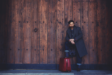 estacion de tren: Retrato de hombre de confianza de barba con estilo con la maleta de la vendimia que se coloca en un fondo de pared de madera con copia espacio para su mensaje de texto o contenido, modelo masculino con mirada de confianza presenta al aire libre