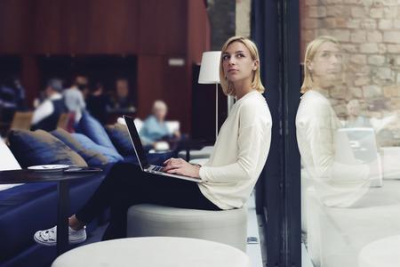 Persona de sexo femenino pensativo que se sienta en la moderna cafetería con portátil abierto entre la muchacha del estudiante de ordenador haciendo el trabajo del curso en su ordenador portátil en la biblioteca, joven mujer de negocios en la rotura de trabajo de trabajo Foto de archivo - 58048853