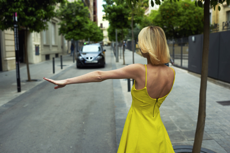 yellow dress: Back view young sexy woman in yellow dress hailing a cab taxi standing on the road with trees, young female tourist with hand gesture stopping taxi in urban setting, businesswoman calling taxi auto