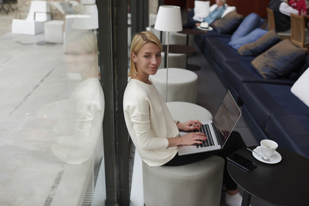 netbook: Gorgeous young woman sitting with open laptop computer in modern coffee shop or hotel interior, female freelancer using net-book for her distance work, student girl learning via portable gadget device