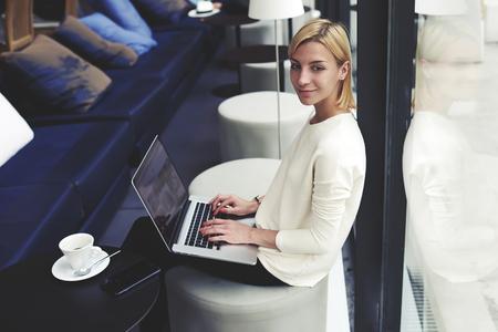Mujer joven magnífica que se sienta con el ordenador portátil abierto en la cafetería moderna o interior del hotel, profesional independiente hembra de uso de red-libro para su trabajo a distancia, chica aprendizaje de los estudiantes a través del dispositivo aparatos portátiles Foto de archivo - 58048924