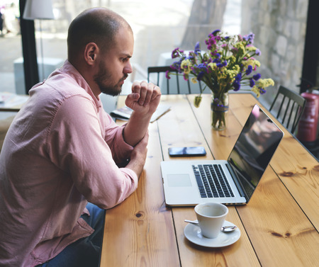 Thoughtful businessman work on notebook while sitting at wooden table in modern coffee shop interior, student reading text or book in cafe, male freelancer connecting to wireless via laptop computer Stock fotó