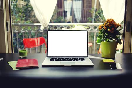 ganancias: Lugar de trabajo con el ordenador abierto, cuadernos de colores y pegatinas, un ordenador portátil con copia espacio pantalla vacía en blanco para su contenido o mensaje de texto, tabla moderna en la ventana abierta en el interior de una casa en verano, el filtro