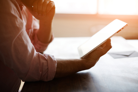 Átgondolt hím ember keresi a digitális tábla képernyőn ülve modern tetőtér többek az asztalnál, tapasztalt vállalkozó olvasás egy szöveget, vagy elektronikus könyv az irodában, szűrő nap