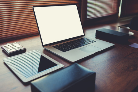 wealthy lifestyle: Laptop computer with white blank copy space screen for text message or publicity content lying on wooden table with digital tablet and stylish accessories,electronic business and distance work concept