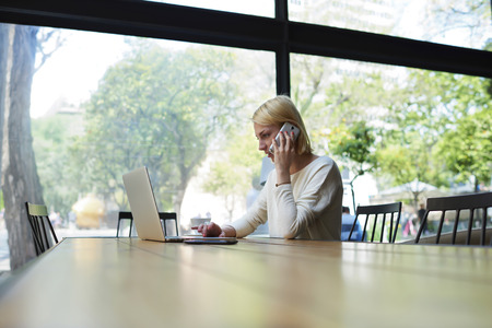 Female freelancer or student working busy on net-book, experienced young businesswoman keyboarding on her laptop computer while talking on smartphone sitting in modern office interior or coffee shop