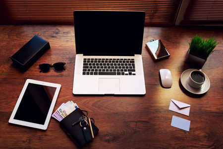 coursework: Top view of modern businessman or entrepreneur workspace with style accessories, euro bills, cup of coffee, open laptop computer and digital tablet with white blank copy space screen, filtered image Stock Photo