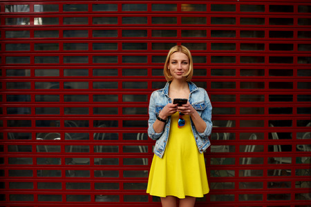 prettiness: Pretty young woman chatting on her smartphone against blank copy space bright background for your content or text message,smiling female hipster in the dress using mobile phone for connect to wireless