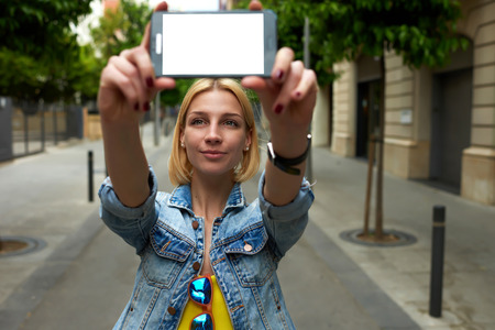 self   portrait: Young female holding smartphone with blank copy space area for your text message or content, tourist woman making self portrait with mobile phone digital camera during her vacation holidays in summer