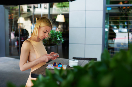 sidewalk talk: Lovely young woman sending text message with her mobile phone, charming hipster girl chatting on cell phone standing at coffee shop, female tourist connecting to wireless on telephone for navigation Stock Photo