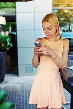 sidewalk talk: Cropped image of lovely young woman sending text message with mobile phone, charming hipster girl chatting on cell phone standing at coffee shop, female student connecting to wireless on telephone