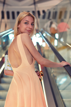 good looking model: Attractive young woman wearing a bright color dress with while standing on escalator in commercial center, sexy female with beautiful figure in short looking to the camera with smile, ready to shop