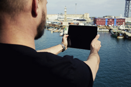 Male tourist with digital tablet camera taking picture of beautiful city from viewpoint, young man photographing marina port city with touch pad, vacation holidays memories