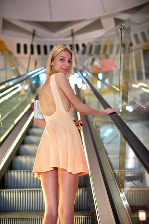 Attraente giovane donna che indossa un abito di colore brillante con mentre in piedi sulla scala mobile nel centro commerciale, femminile sexy con la bella figura in breve osserva alla macchina fotografica con un sorriso, pronto a fare acquisti
