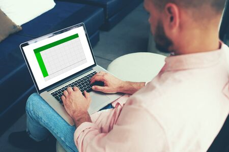 capital gains: Rear view experienced businessman sitting front laptop computer with copy space chart for your information on screen, young entrepreneur working with statistics data on netbook while keyboarding text