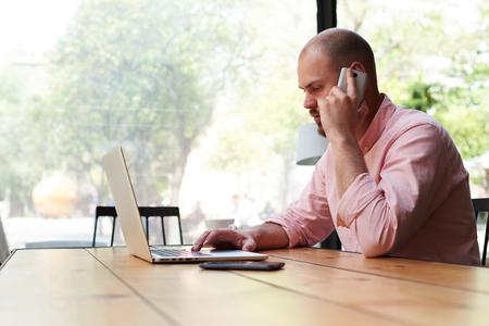 잘 생긴 비즈니스 남자 스마트 전화 얘기하고 노트북 화면, 현대 프리젠 테이션 나무 테이블의 컴퓨터에서 작업하는 남성 프리랜서 로프트, 젊은 hipster 스톡 콘텐츠