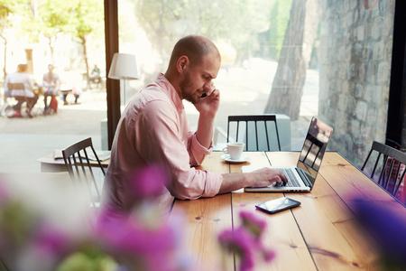 컴퓨터 화면에서 스마트 폰, 젊은 비즈니스 남자 사용에 대 한 얘기는 남성 학생 작업 현대 커피가 게의 나무 테이블에 앉아 노트북, hipster 로프트 공간