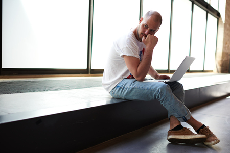 coursework: Young man looking thoughtful while working on laptop computer holding it on the knees, university student using notebook for write his coursework, freelancer sitting in modern interior thinking about