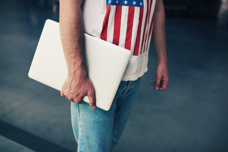 Cropped image university student holding metal color compact notebook in the hand, young freelancer or businessman hands holding close laptop computer, copy space for your text message, filtered image