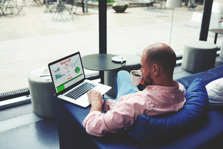 capital gains: Experienced businessman sitting front laptop computer with financial information as graphics and charts, young entrepreneur work on netbook drinking cafe of cup while he sitting in modern coffee shop