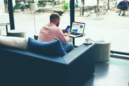 Fiatal, Ügy, elfoglalt, dolgozó, laptop számítógép és az okostelefon ül kanapé modern kávézóban vagy szállodában hall, vállalkozó elemzése a pénzügyi információkat a grafika és a grafikonokat füzetében Stock fotó