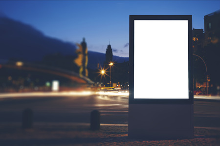 advertising space: Illuminated blank billboard with copy space for your text message or content, public information board in night city with beautiful dusk on background, advertising mock up banner in metropolitan city