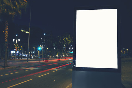 comercial: Illuminated blank billboard with copy space for your text message or content, public information board in night city with beautiful dusk on background, advertising mock up banner in metropolitan city
