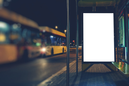 Illuminated blank billboard with copy space for your text message or content, advertising mock up banner of bus station, public information board in night city, auto bus stop empty poster Banco de Imagens