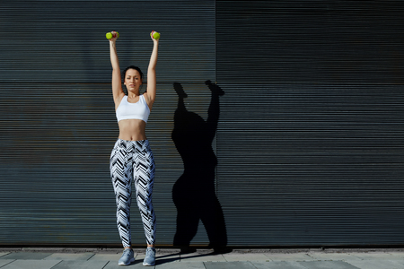 area sexy: Athletic gorgeous young woman lifting weights standing with arms up against black wall background at sunset, attractive female working on her arms outdoors against copy space for your text message Stock Photo