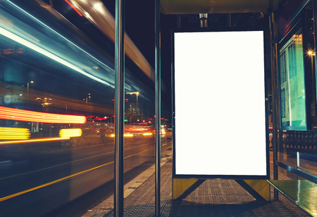 parada de autobus: Iluminado cartelera en blanco, con copia espacio para su mensaje de texto o contenido, publicidad maqueta bandera de la estaci�n de autobuses, tabla de informaci�n p�blica con veh�culos enmascarados en alta velocidad en la ciudad de noche Foto de archivo