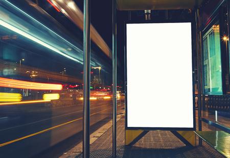Oświetlony pusty billboard z miejsca kopiowania dla wiadomości tekstowej lub treści, reklamy makiety sztandar dworca autobusowego, tablicy informacyjnej publicznego z niewyraźne pojazdów w dużej prędkości w nocy miasta