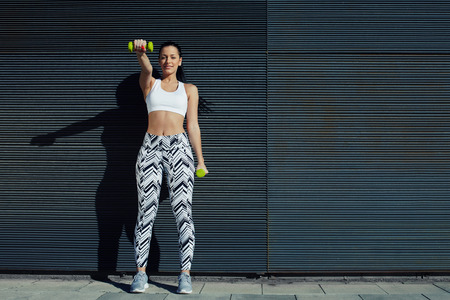 tense: Sporty young woman lifting weights standing with arms tense against black wall outdoors, female working on her arms training bicep curls with copy space background for your text message by side