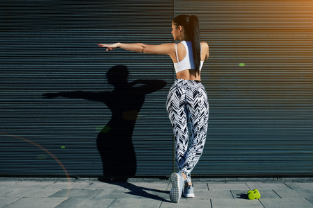 area sexy: Back view athletic woman with perfect figure and buttocks shape exercising against wall with copy space for your text message, fit female in sportswear working out stretching on background outdoors