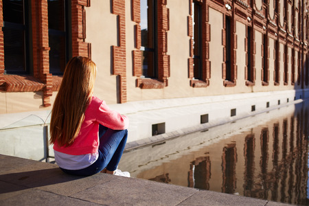 negative area: Rear view young female looking thoughtful as sitting on the steps alone, young woman suffering from loneliness and depression, trendy hipster enjoying sunny afternoon outdoors, teenager relaxing