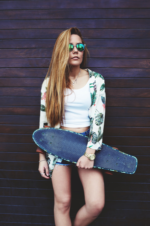 area sexy: Portrait of casually-dressed female hipster holding skateboard while she standing on wooden wall background in summer, young trendy woman in sunglasses posing with her longboard enjoying good day Stock Photo