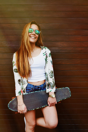 area sexy: Smiling teenage girl in sunglasses holding her skateboard while standing against wooden wall background, casually-dressed female hipster with beautiful figure posing with longboard in summer