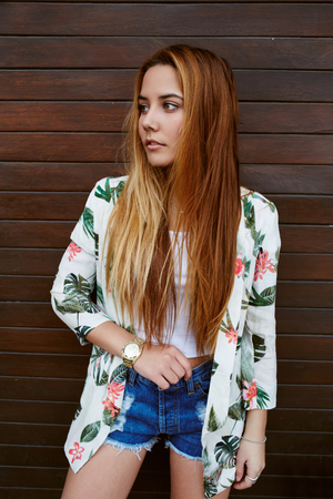 prettiness: Portrait of a beautiful hipster girl wearing trendy clothing standing on wooden wall background, fashionable and stylish young woman with long hair posing outdoors in summer Stock Photo