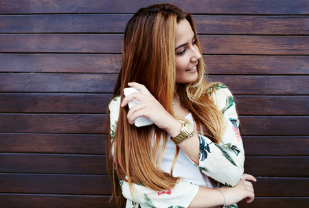 prettiness: Attractive laughing female standing with mobile phone against wooden wall background with copy space area, pretty casually-dressed hipster woman looking away smiling and feeling so happy in joy