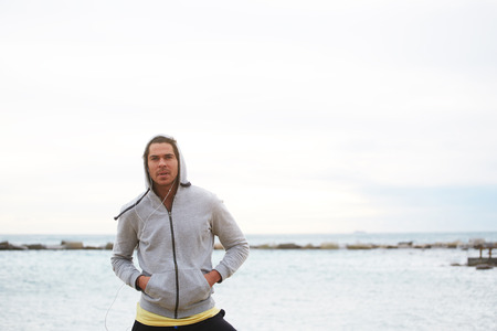 Portrait of sporty caucasian man resting during his training on the beach while listening to music with headphones, attractive male runner dressed in sweatshirt standing on sea horizon background