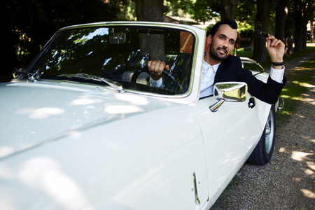 40 year old man: Successful and wealthy businessman sitting behind the wheel of his luxury cabriolet car on countryside road, sure and confident handsome man sits in his new convertible car outdoors looking so happy Stock Photo