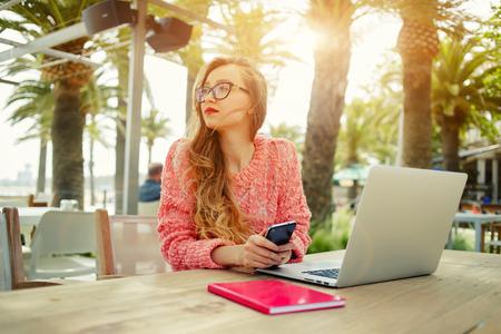 freelancer femme Attractive tenir téléphone intelligent assis à la table d'entrée en bois ordinateur ouvert à café moderne, jeune femme travail créatif sur ordinateur portable tout en ayant le petit déjeuner sur la terrasse, flare soleil Banque d'images