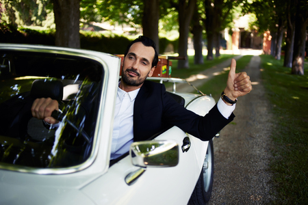 Successful and wealthy businessman sitting behind steering wheel of luxury cabriolet car on countryside road, confident handsome man sits in his new convertible car doing super gesture with the finger
