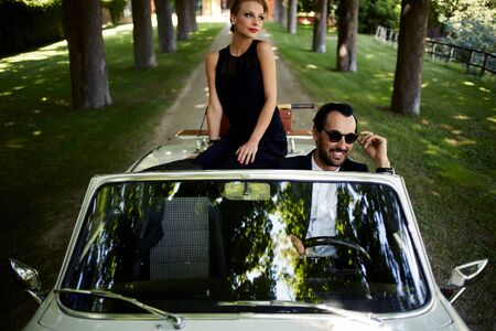 rich people: Happy couple enjoying a ride on their luxury convertible in the summer,gorgeous rich woman feels so glad while they riding on cabriolet with sure handsome brunette man, romantic couple at journey trip