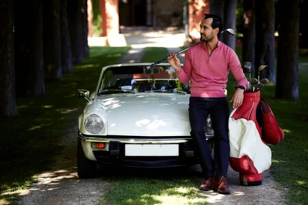 rich people: Handsome golf player holding a driver or golf club while getting ready for a day on the course, just arrived on his convertible luxury car wealthy man preparing for golf game at his recreation time