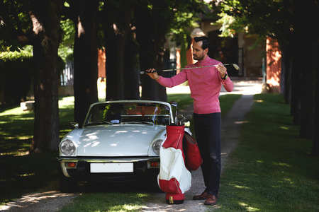 just arrived: Handsome golf player holding a driver or golf club while getting ready for a day on the course, just arrived on his convertible luxury car wealthy man preparing for golf game at his recreation time
