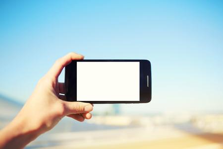 Vrouwelijke hand met smartphone met lege kopie ruimte voor uw SMS-bericht of inhoud, toeristische hand met mobiele telefoon tijdens het nemen van een foto van landschap in de zomer reizen, leeg digitaal scherm Stockfoto