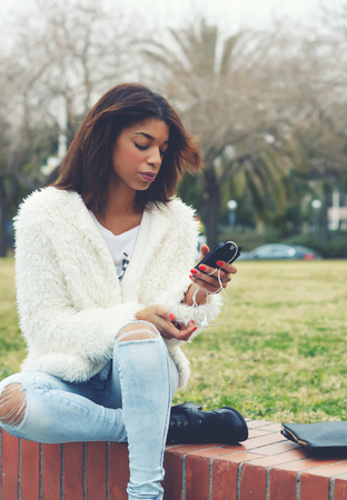 tryst: Stylish hipster girl holding smart phone while sitting in the park outdoors, attractive afro american woman using cell phone while chatting or reading text message, young teenager holding mobile phone