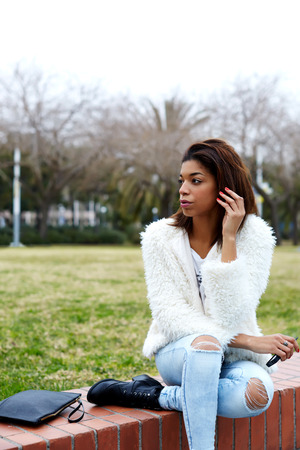 waiting glance: Portrait of trendy female hipster dressed in stylish clothing ready for tryst waiting for someone hold smart phone in the hand, young afro american woman sitting in beautiful park looking away