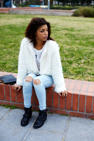 Attractive female hipster dressed in cute stylish clothing sitting outdoors in the park, fashionable black woman waiting for someone for recreation promenade at weekend