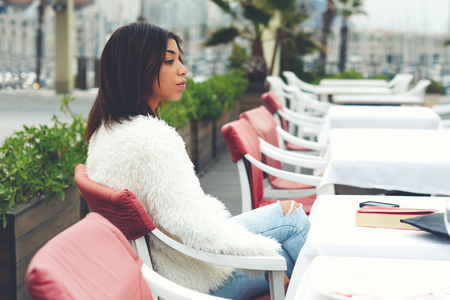 tryst: Portrait of attractive afro american woman enjoying a good day in restaurant while sitting at the table, charming female hipster sitting on the terrace of sidewalk cafe with palm tree on background Stock Photo